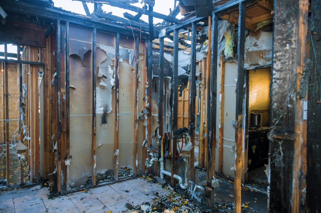 Burnt wooden walls house with charred roof burnt fire damaged interior details